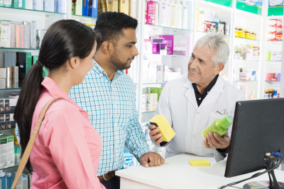 Smiling pharmacist showing products to multiethnic couple at checkout counter in pharmacy