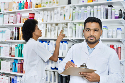 Portrait of confident male pharmacist holding clipboard while female colleague arranging stock in pharmacy